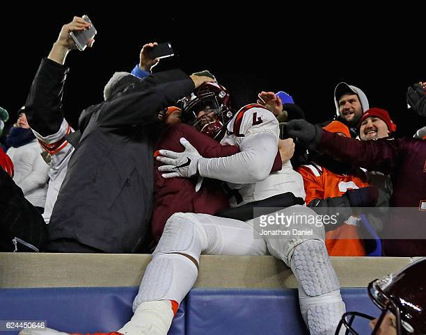Jerod Evans of the Virginia Tech Hokies celebrates in the stands with fans against the Notre Dame Fighting Irish teammate Wright Bynum after a win...