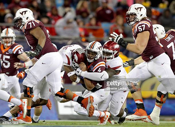 Jerod Evans of the Virginia Tech Hokies is tackled by the Arkansas Razorbacks during the Belk Bowl at Bank of America Stadium on December 29 2016 in...
