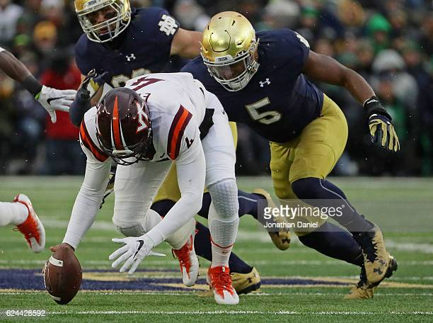 Jerod Evans of the Virginia Tech Hokies moves to recover a teammates fumble in front of Nyles Morgan of the Notre Dame Fighting Irish at Notre Dame...