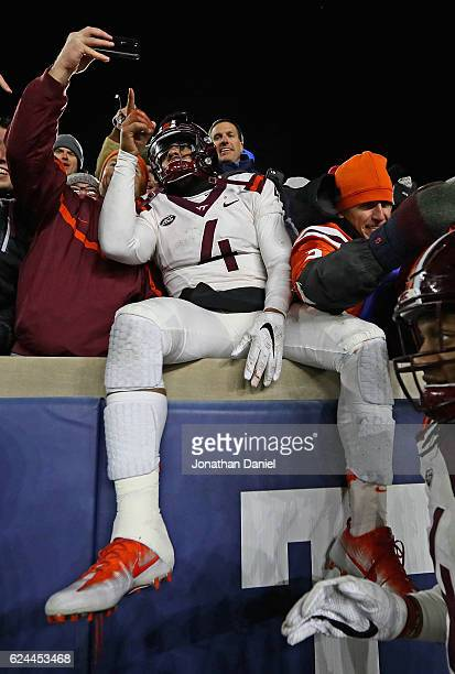 Jerod Evans of the Virginia Tech Hokies poses for a 'selfie' in the stands with fans after a win over the Notre Dame Fighting Irish at Notre Dame...