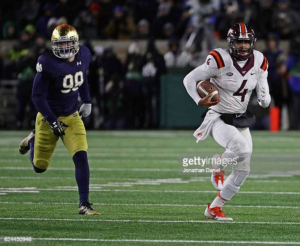 Jerod Evans of the Virginia Tech Hokies runs for a first down chassed by Jerry Tillery of the Notre Dame Fighting Irish at Notre Dame Stadium on...