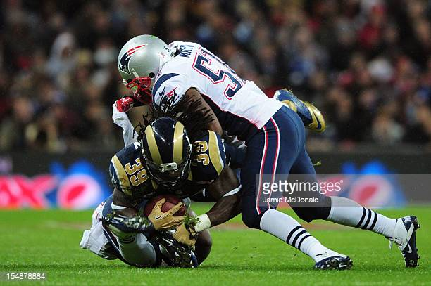 Jerod Mayo of the New England Patriots tackles Steven Jackson of the St Louis Rams during the NFL International Series match between the New England...