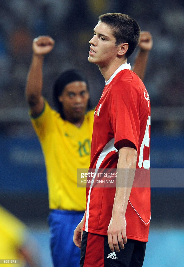 Jeroen Simaeys of Belgium (R) reacts as Ronaldinho of Brazil celebrates a goal during the 2008 Beijing Olympic Games men's football bronze medal match in Shanghai on August 22, 2008. Brazil won 3-0. AFP PHOTO/HOANG DINH Nam