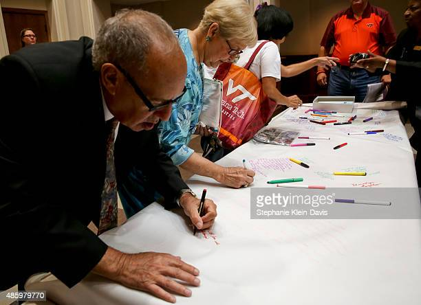 Jerold Franks of Roanoke and Bootie Bell Chewning sign a large roll of paper with words and prayers for the families of Alison Parker and Adam Ward...