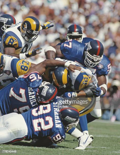 Jerome Bettis Running Back for the Los Angeles Rams is tackled by Corey Miller Michael Strahan and Keith Hamilton of the New York Giants as he tries...