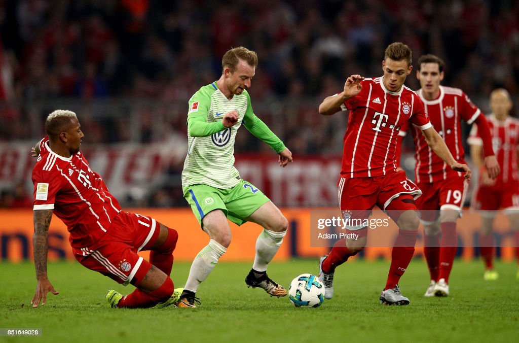 Jerome Boateng (L) and Joshua Kimmich (R) of Muenchen and Maximilian Arnolf of Wolfsburg battle for the ball during the Bundesliga match between FC Bayern Muenchen and VfL Wolfsburg at Allianz Arena on September 22, 2017 in Munich, Germany.