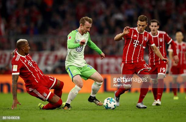 Jerome Boateng and Joshua Kimmich of Muenchen and Maximilian Arnolf of Wolfsburg battle for the ball during the Bundesliga match between FC Bayern...
