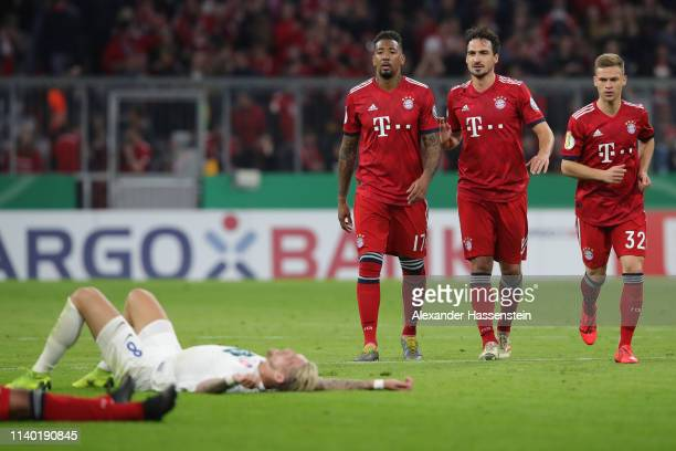 Jerome Boateng Mats Hummels and Joshua Kimmich of Muenchen and Marc Schnatterer of Heidenheim react after the DFB Cup quarterfinal match between...