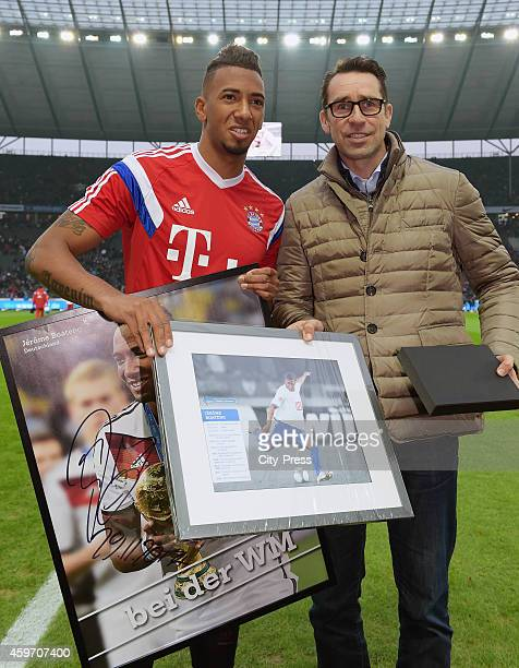 Jerome Boateng of Bayern Muenchen and CEO Michael Preetz of Hertha BSC pose for photos on the pitch prior to the Bundesliga match between Hertha BSC...