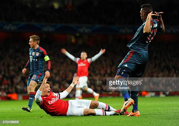 Jerome Boateng of Bayern Muenchen brings down Mesut Oezil of Arsenal in the area for a penalty during the UEFA Champions League Round of 16 first leg...