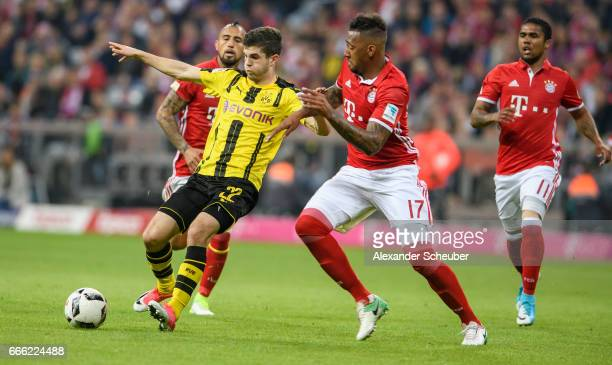 Jerome Boateng of Bayern Muenchen challenges Christian Pulisic of Dortmund during the Bundesliga match between Bayern Muenchen and Borussia Dortmund...