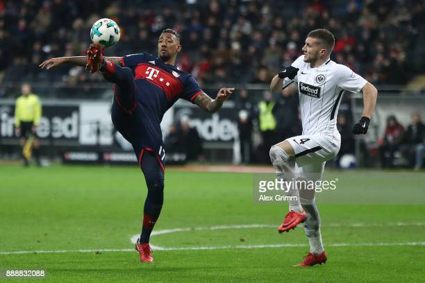 Jerome Boateng of Bayern Muenchen handles the ball while Ante Rebic of Frankfurt looks on during the Bundesliga match between Eintracht Frankfurt and...