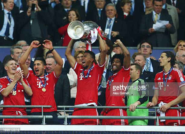 Jerome Boateng of Bayern Muenchen lifts the trophy in celebration alongside team mates after victory in the UEFA Champions League final match between...