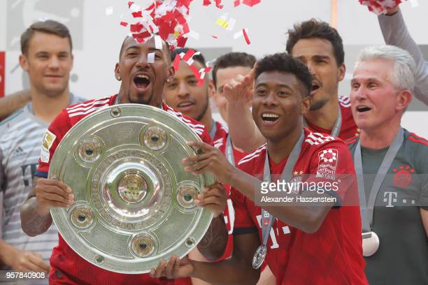 Jerome Boateng of Bayern Muenchen lifts with his team mate David Alaba the trophy in Celebration for winning the German Champiosnhip title after the...
