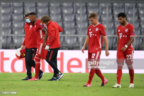 Jerome Boateng of Bayern Munich is helped of the pitch by medical staff after sustaining an injury during the UEFA Champions League round of 16...