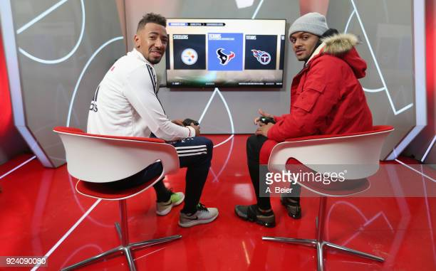 Jerome Boateng of FC Bayern Muenchen and NFL player Deshaun Watson of Houston Texans smile as they play a computer game after a training session at...
