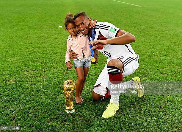 Jerome Boateng of Germany poses for photographs with his daughter and the World Cup trophy after the 2014 FIFA World Cup Brazil Final match between...