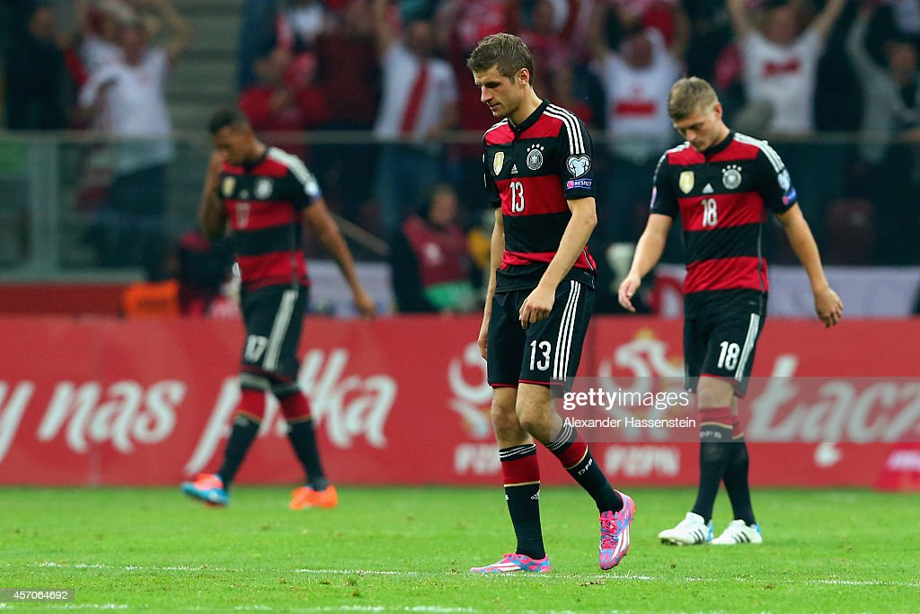 Jerome Boateng (L) of Germany recats with his team mates Thomas Mueller and Toni Kroos (R) after receiving the first goal during of the EURO 2016 Group D qualifying match between Poland and Germany at Narodowy Stadium on October 11, 2014 in Warsaw, Poland.