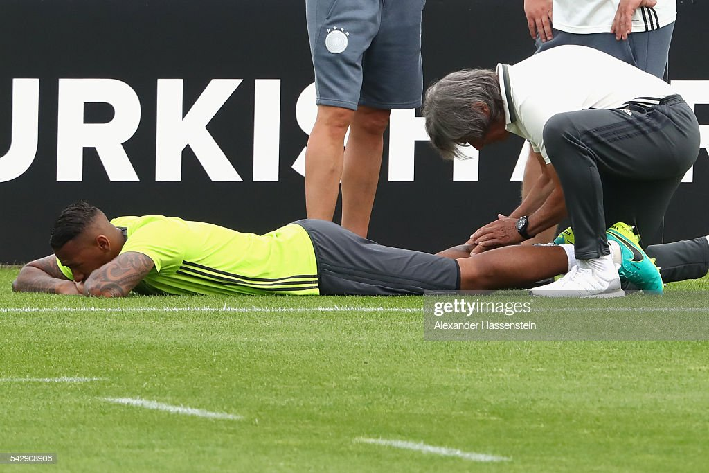 Jerome Boateng of Germany receives medical treatment from team doctor Hans-Wilhelm Mueller-Wohlfahrt during a Germany training session ahead of their Euro 2016 round of 16 match against Slovakia at Ermitage Evian on June 25, 2016 in Evian-les-Bains, France.