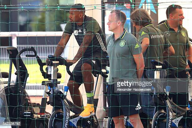 Jerome Boateng of Germany warming up on a stationary bike next to team doctor HansWilhelm MuellerWohlfahrt during a Germany training session at...