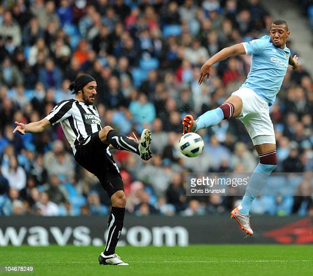 Jerome Boateng of Manchester City jumps for a high ball with Jonas Gutierrez of Newcastle United during the Barclays Premier League match between...