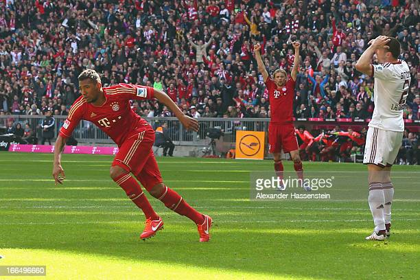 Jerome Boateng of Muenchen celebrates scoring the opening goal with his team mate Anatoliy Tymoshchuk whilst Timmy Simons of Nuernberg reacts during...