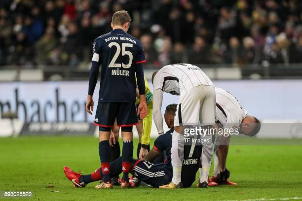 Jerome Boateng of Muenchen on the ground and KevinPrince Boateng of Frankfurt helps during the Bundesliga match between Eintracht Frankfurt and FC...