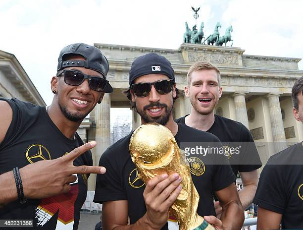 Jerome Boateng Sami Khedira and Per Mertersacker celebrate during the German team victory ceremony on July 15 2014 in Berlin Germany Germany won the...