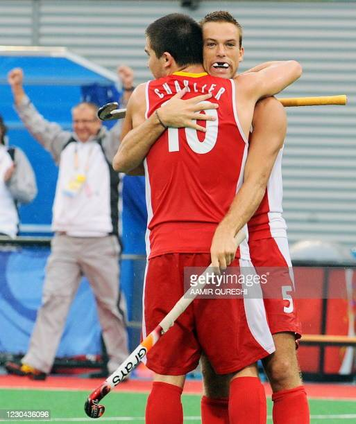 Jerome Dekeyser celebrates with teammate Cedric Charlier of Belgium after scoring a goal against Canada during their men's field hockey qualifying...