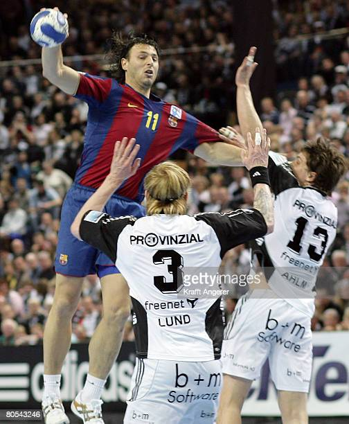 Jerome Fernandez of Barcelona challenges for the ball with Boerge Lund and Marcus Ahlm of Kiel during the EHF Champions League semi final match...