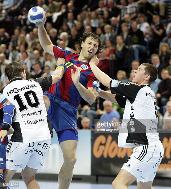 Jerome Fernandez of Barcelona challenges for the ball with Stefan Loevgren and Kim Andersson of Kiel during the EHF Champions League semi final match...