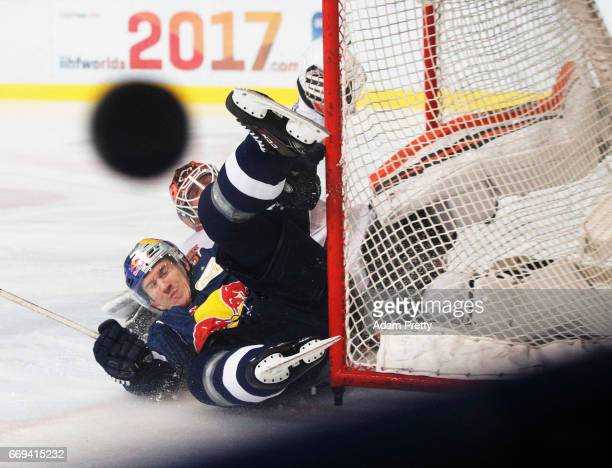 Jerome Flaake of Muenchen is smashed and earns a pentalty goal during the DEL PlayOffs Final Match 5 between EHC Muenchen and the Grizzlys Wolfsburg...
