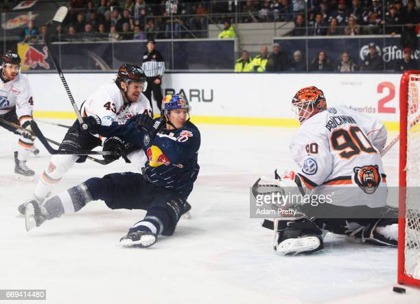 Jerome Flaake of Muenchen is smashed by Alexander White of Wolfsburg and earns a pentalty goal during the DEL PlayOffs Final Match 5 between EHC...