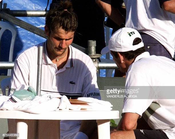 Jerome Golmard of France confers with team technician Guy Forget during his Davis Cup World Group first round match against Brazil's Gustavo Kuerten...