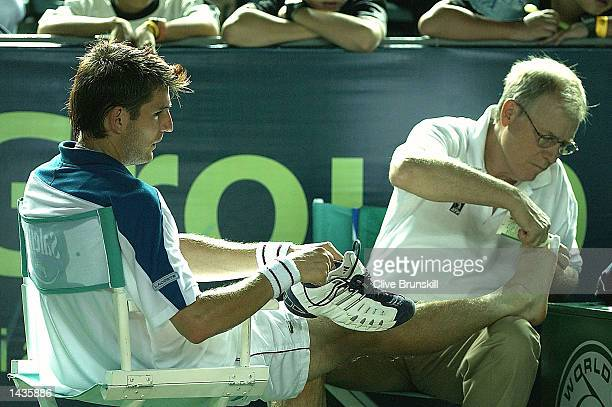 Jerome Golmard of France gets treatment for a foot injury during his straight sets defeat by Juan Carlos Ferrero of Spain during the semifinal of the...