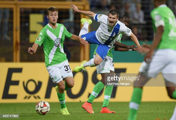 Jerome Gondorf of Darmstadt in action against Robin Knoche of Wolfsburg and Josuha Guilavogui of Wolfsburg during the DFB Cup first round match...