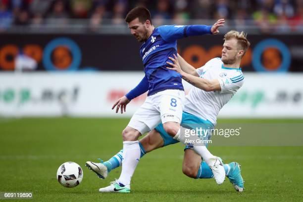 Jerome Gondorf of Darmstadt is challenged by Johannes Geis of Schalke during the Bundesliga match between SV Darmstadt 98 and FC Schalke 04 at...