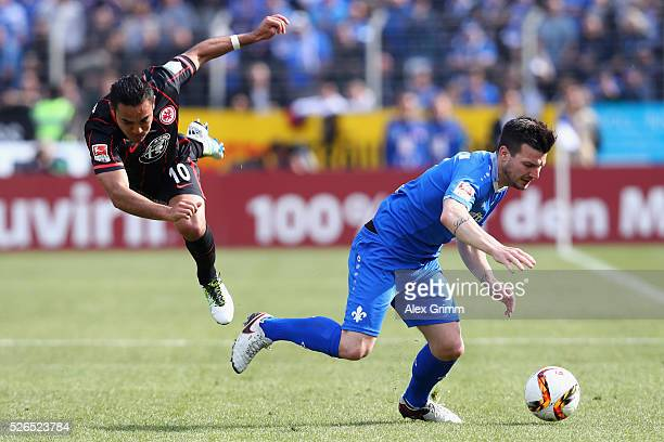Jerome Gondorf of Darmstadt is challenged by Marco Fabian of Frankfurt during the Bundesliga match between SV Darmstadt 98 and Eintracht Frankfurt at...