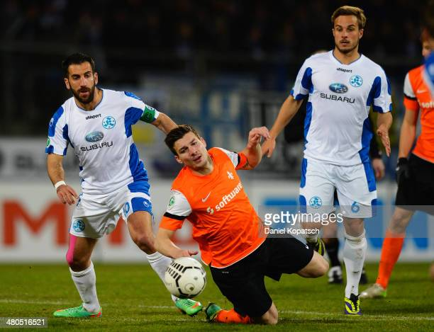 Jerome Gondorf of Darmstadt is challenged by Vincenzo Marchese of Stuttgarter Kickers and team mate Sandrino Braun during the third Bundesliga match...