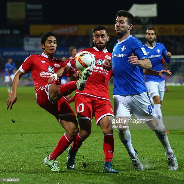 Jerome Gondorf of Darmstadt is challenged by Yunus Malli and Yoshinori Muto of Mainz during the Bundesliga match between SV Darmstadt 98 and 1FSV...