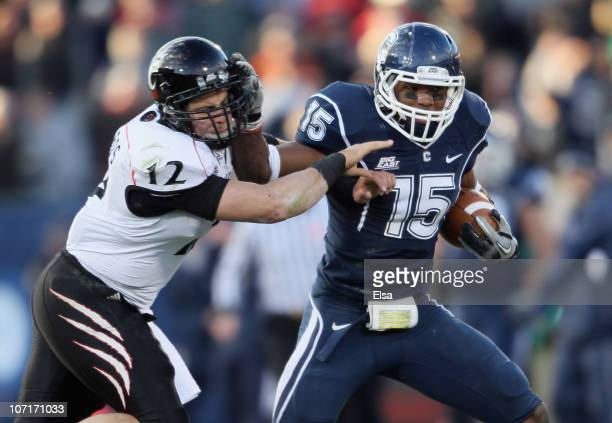 Jerome Junior of the Connecticut Huskies is tackled by Zach Collaros of the Cincinnati Bearcats after Junior intercepted Collaros' pass in the fourth...