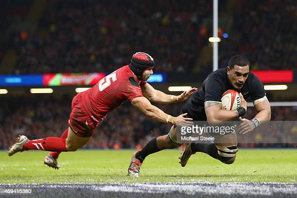 Jerome Kaino of the All Blacks scores his sides second try as Leigh Halfpenny of Wales challenges during the International match between Wales and...
