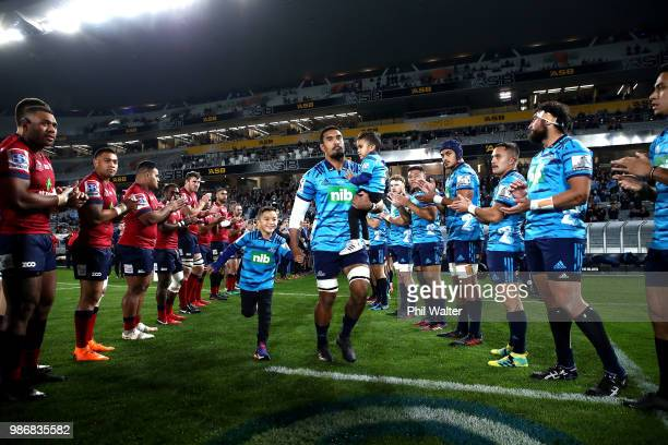 Jerome Kaino of the Blues runs out onto the field with his children during the round 17 Super Rugby match between the Blues and the Reds at Eden Park...