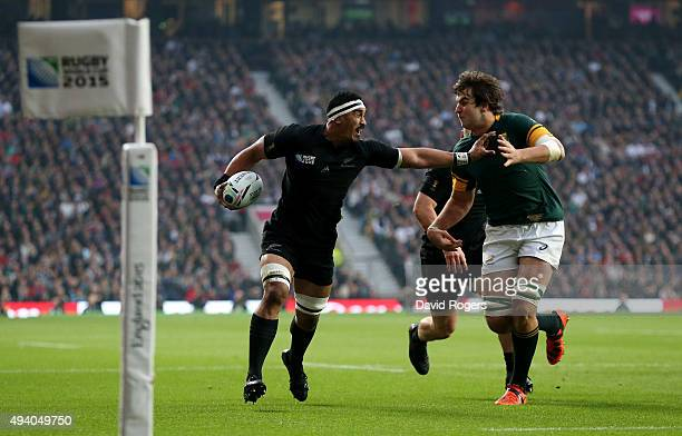Jerome Kaino of the New Zealand All Blacks hands of Lodewyk De Jager of South Africa as runs in the opening try during the 2015 Rugby World Cup Semi...