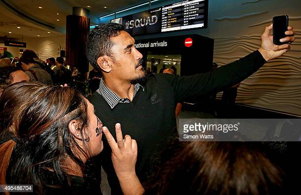 Jerome Kaino of the New Zealand All Blacks takes a selfie with a fan at the Auckland International Airport on November 4 2015 in Auckland New Zealand...