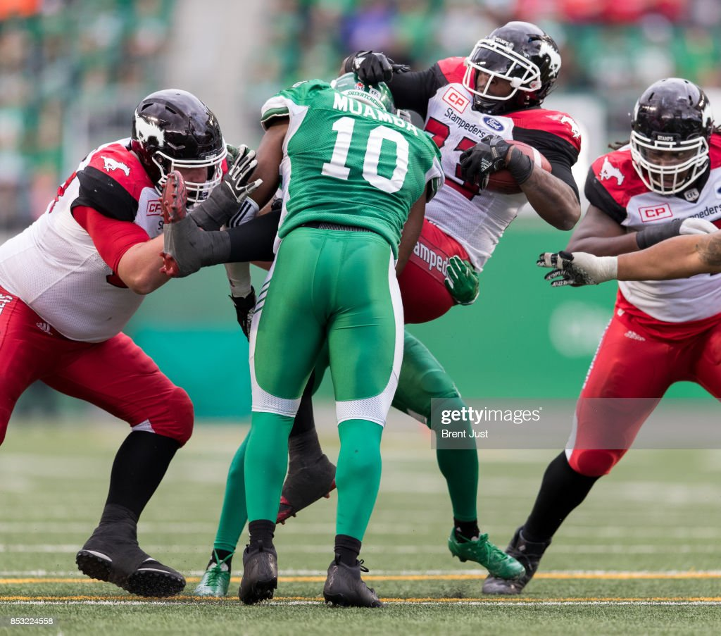 Jerome Messam #33 of the Calgary Stampeders is picked up on a tackle by Henoc Muamba #10 of the Saskatchewan Roughriders in second half action of the game between the Calgary Stampeders and Saskatchewan Roughriders at Mosaic Stadium on September 24, 2017 in Regina, Canada.