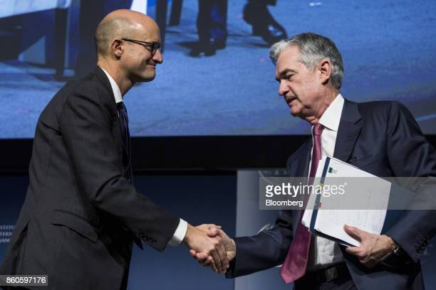 Jerome Powell governor of the US Federal Reserve right shakes hands with Robin Brooks managing director and chief economist of the IIF during the...