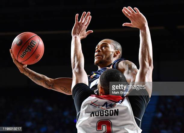 Jerome Randle of the 36ers makes a basket over Darington Hobson of the Hawks during the round 12 NBL match between the Adelaide 36ers and the...