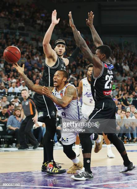 Jerome Randle of the Kings shoots the ball between Josh Boone of United and Casey Prather during the round nine NBL match between Melbourne United...