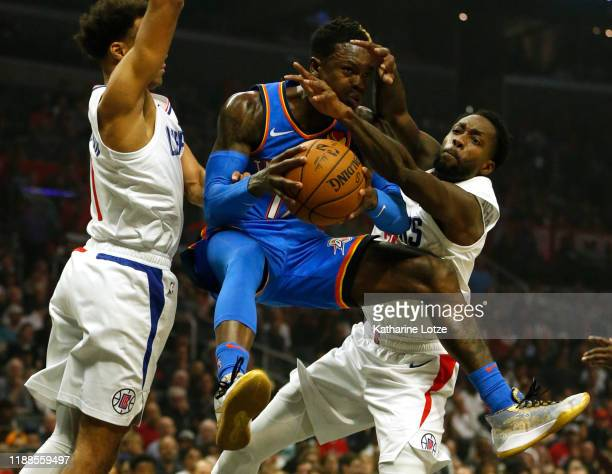 Jerome Robinson and Patrick Beverley of the Los Angeles Clippers defend Dennis Schroder of the Oklahoma City Thunder as he goes up for a basket...